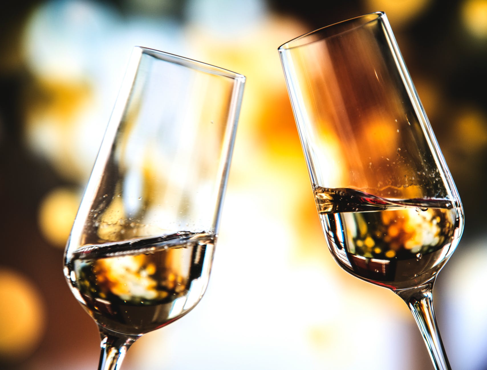 bokeh photo of two toast clear glass wine glasses