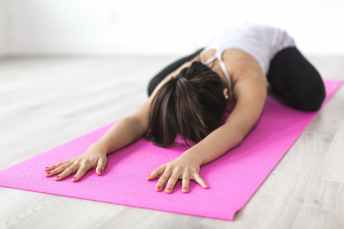 woman doing yoga pose on pink yoga mat